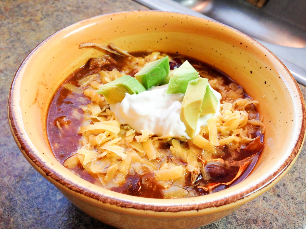 Crockpot Mexican Chili in a yellow bowl topped with sour cream avocado and cheese