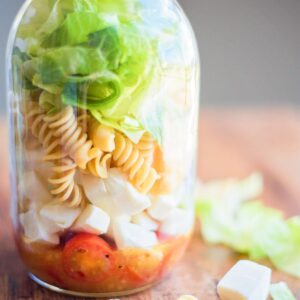 Italian Mason Jar Salad in a jar surrounded by various ingredients on a table