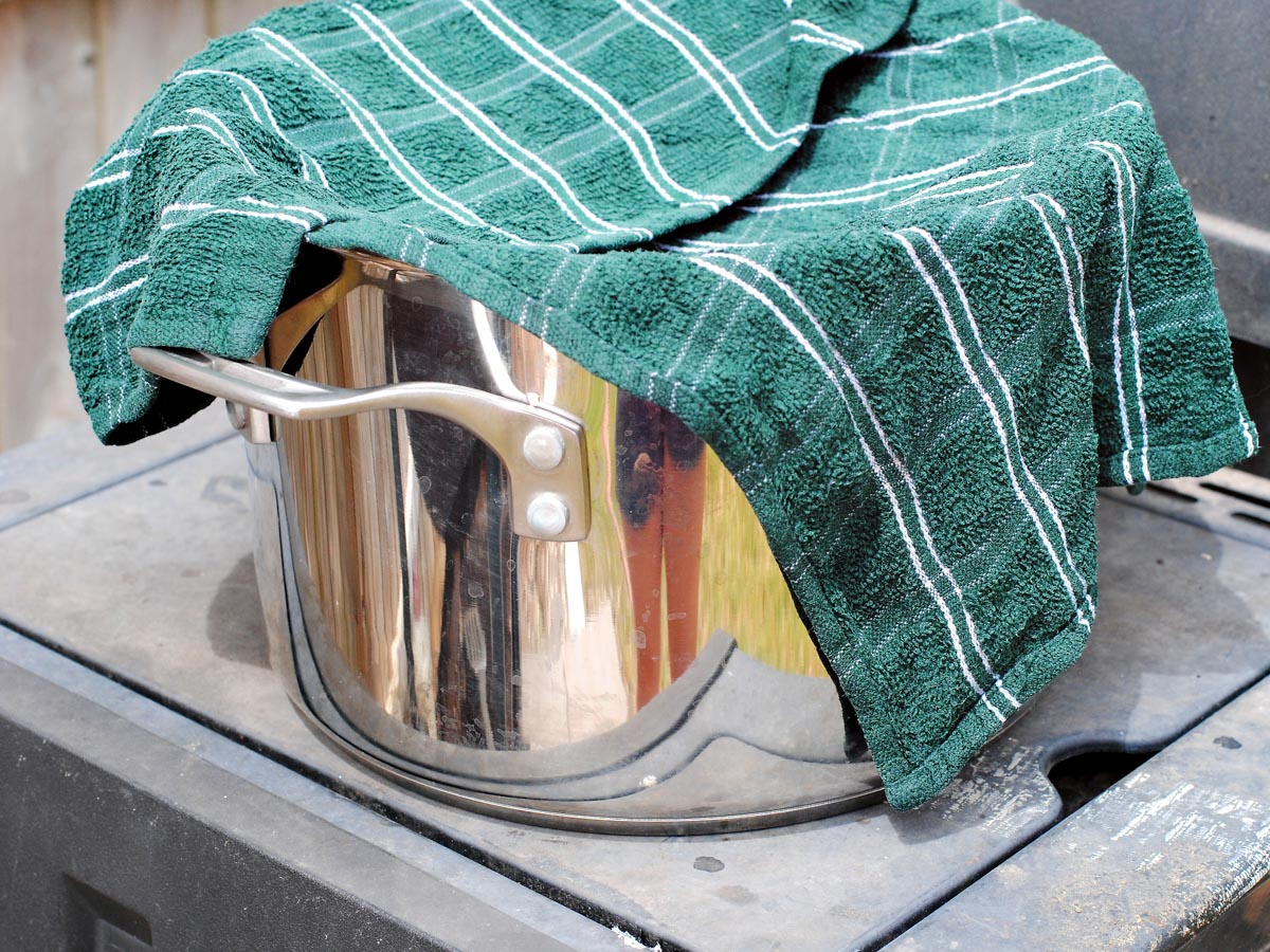 a silver pot with a green dish towel over it