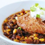 slow cooker salsa chicken in a white bowl topped with sour cream and scallions