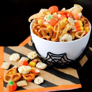 spooky snack mix in a spider bowl with a striped Halloween napkin