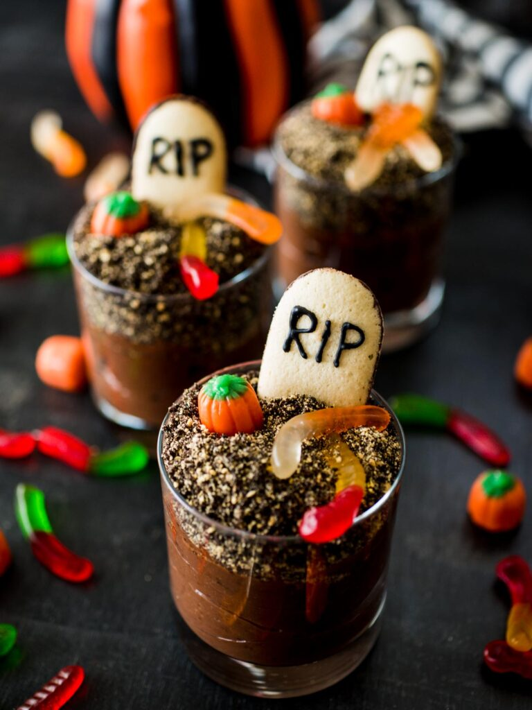 halloween graveyard dirt cups surrounded by toppings