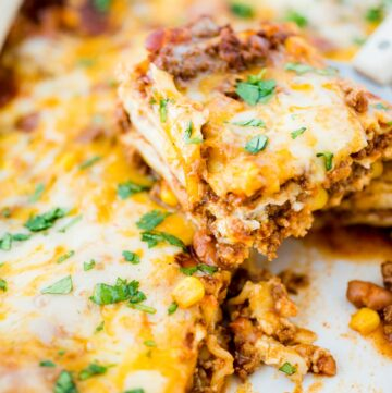 tex mex lasagna being scooped from casserole dish