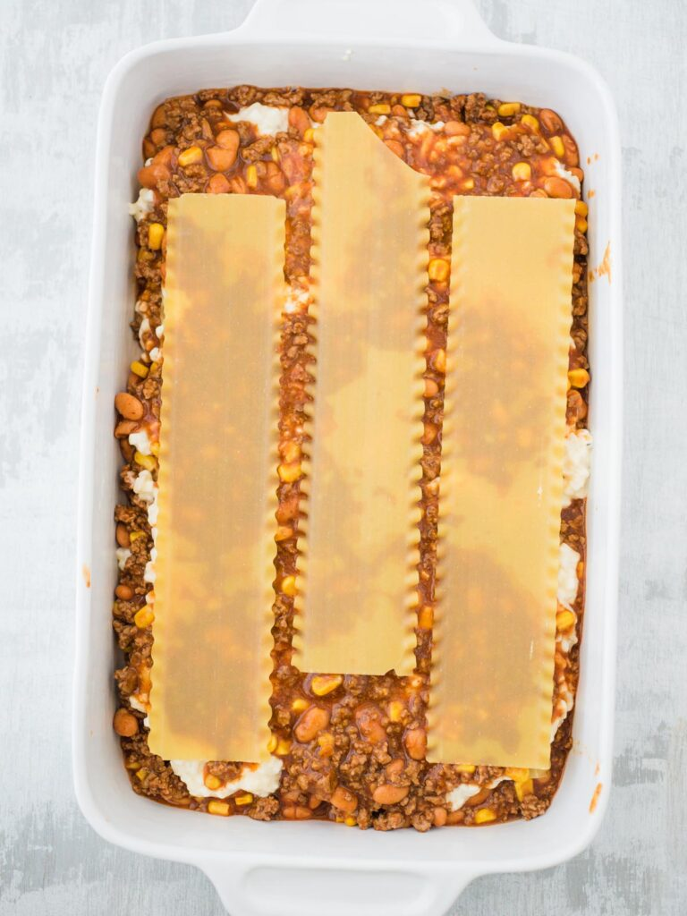 pasta noodle layer of tex mex lasagna in casserole dish