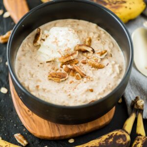 banana overnight oats in bowl topped with whip cream and pecans