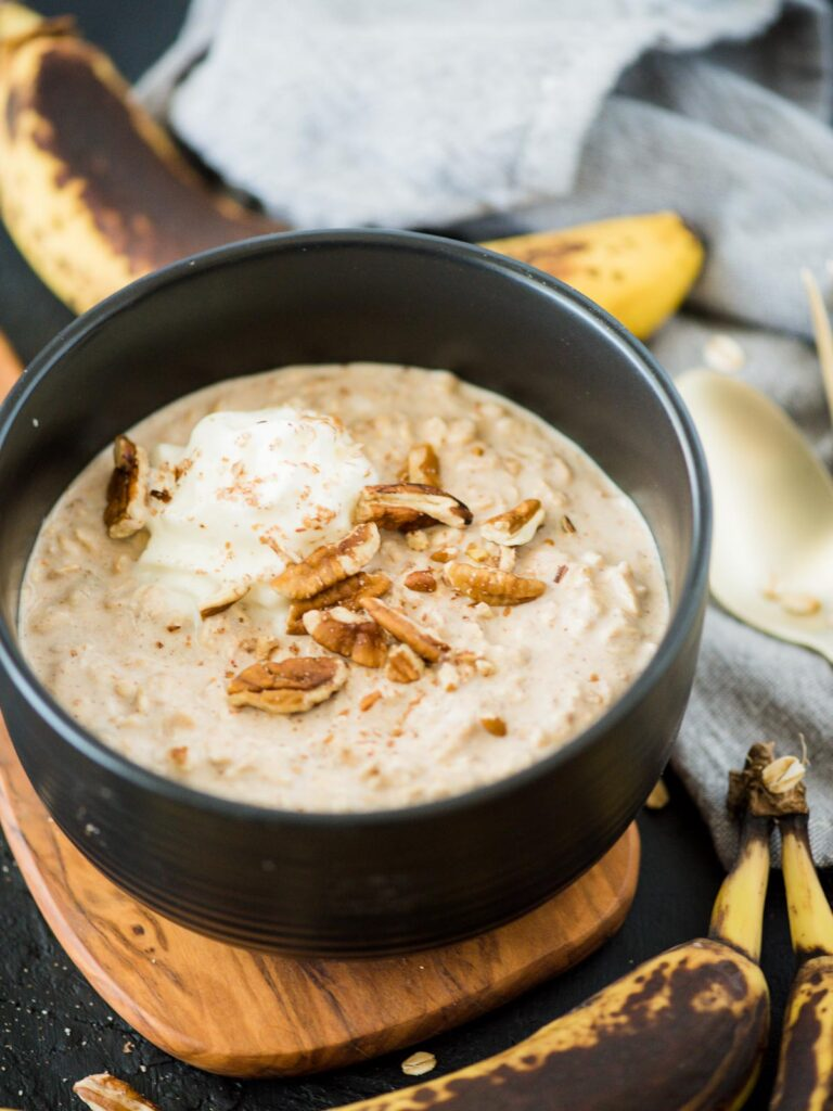 banana bread overnight oats in bowl topped with pecans and whipped cream
