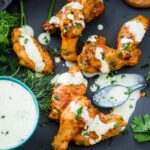 crispy chicken wings in the air fryer sprinkled with parsley and a ranch drizzle