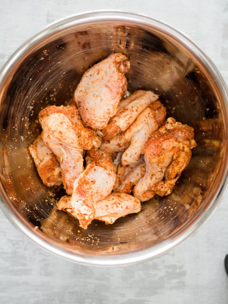 seasoned raw chicken wings in a bowl