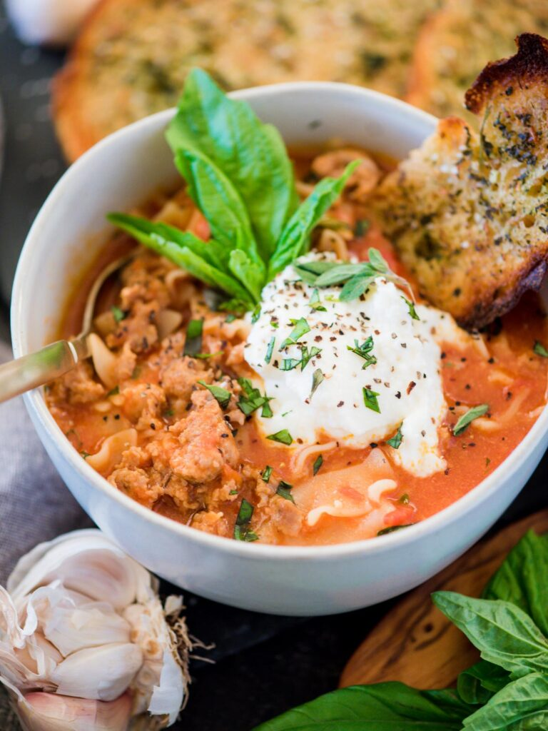 bowl of one-pot lasagna soup topped with basil and ricotta