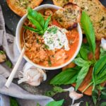 lasagna soup with garlic bread and topped with ricotta and basil