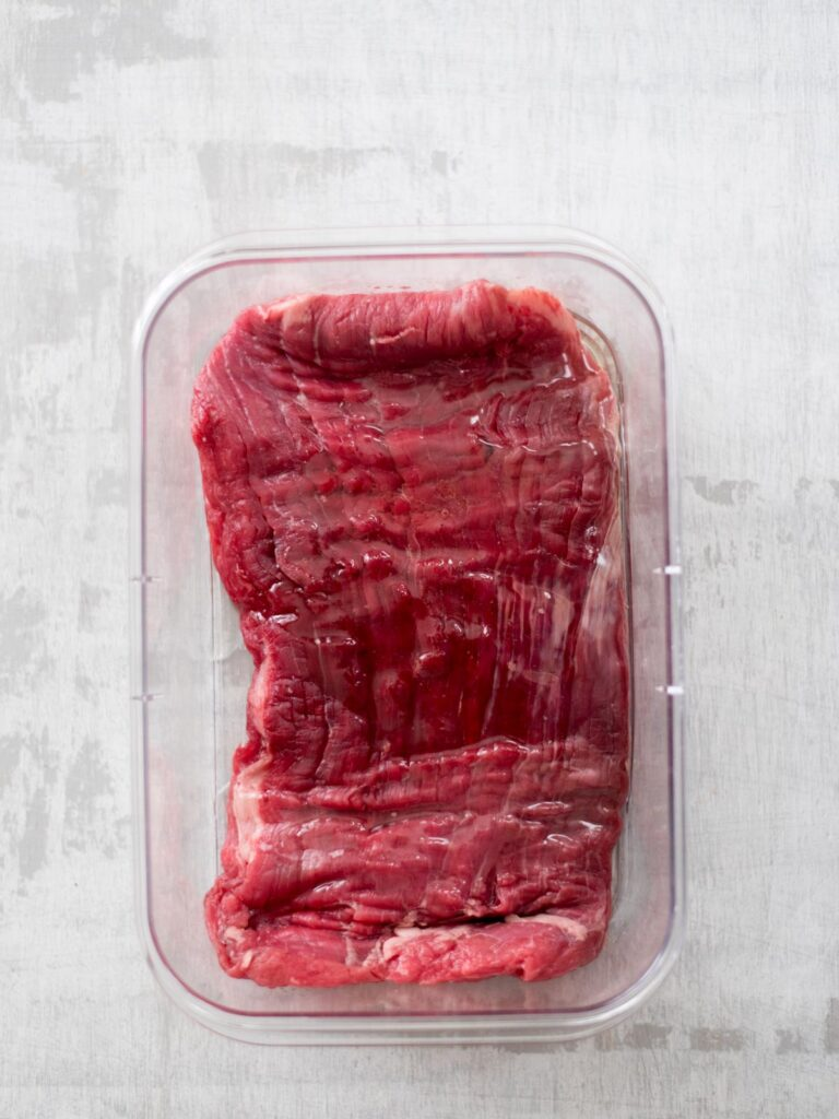 oil added to flank steak in container