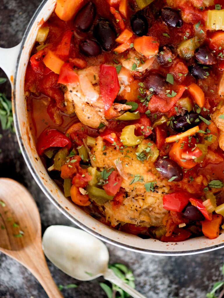 baked chicken cacciatore topped with oregano in a dutch oven