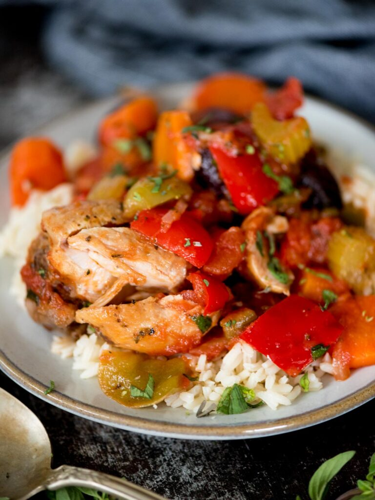 baked chicken cacciatore on top of white rice topped with fresh oregano