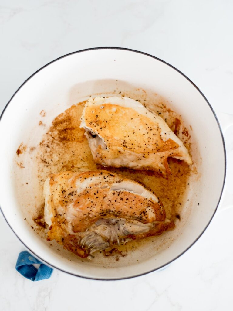 seared chicken inside of a dutch oven