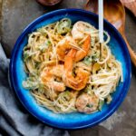 cajun shrimp alfredo in a blue bowl topped with parmesan