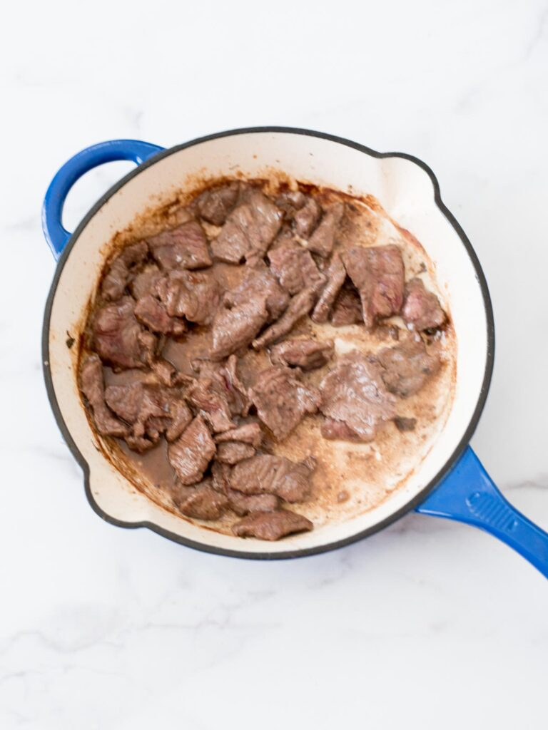 beef cooking in a skillet