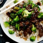 Chinese beef and broccoli served over rice topped with sesame seeds