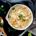 Creamy chicken and rice soup in a bowl topped with parsley and thyme