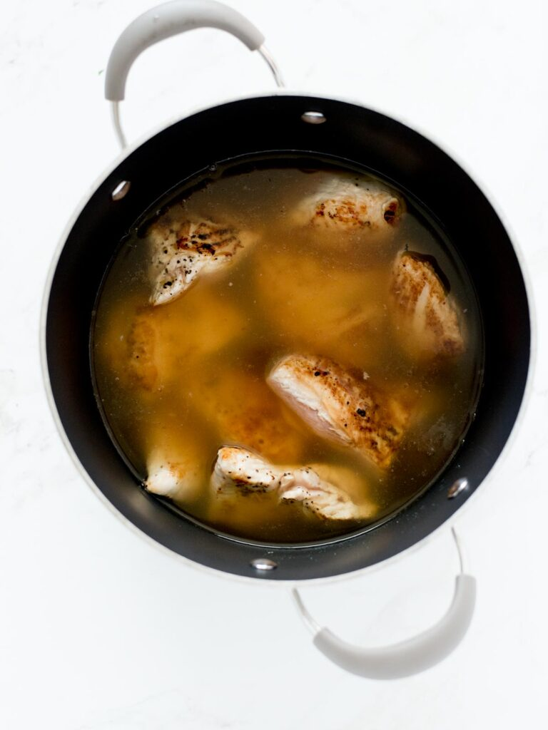 chicken and broth in soup pot