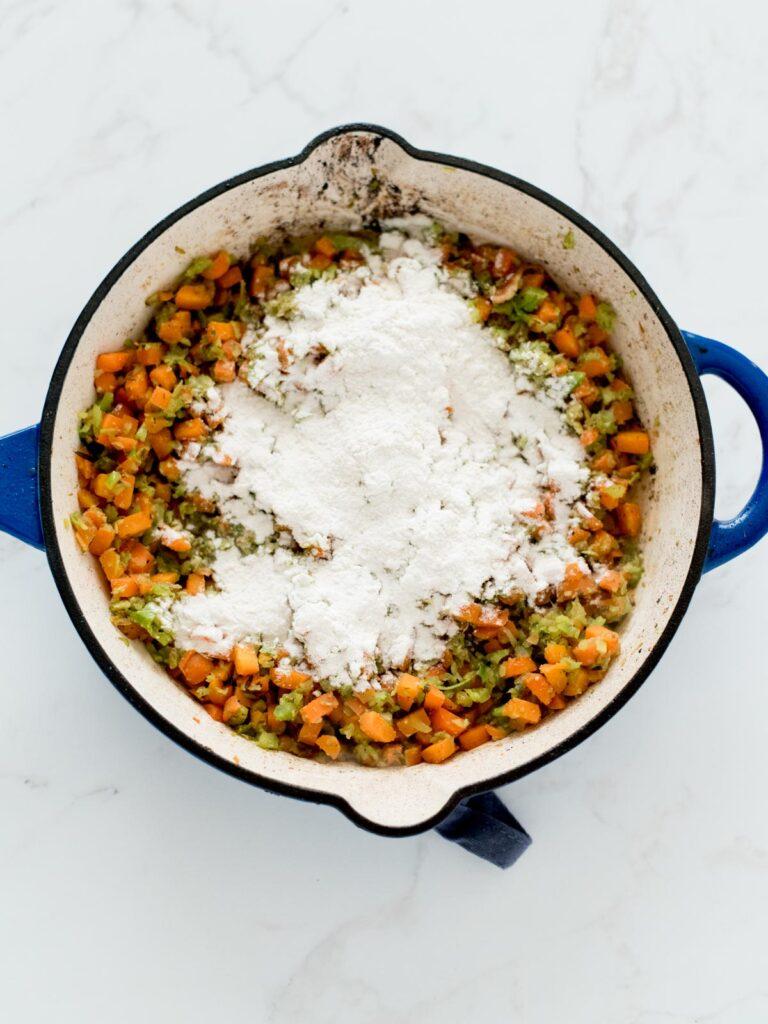 sautéed vegetables in a skillet with flour