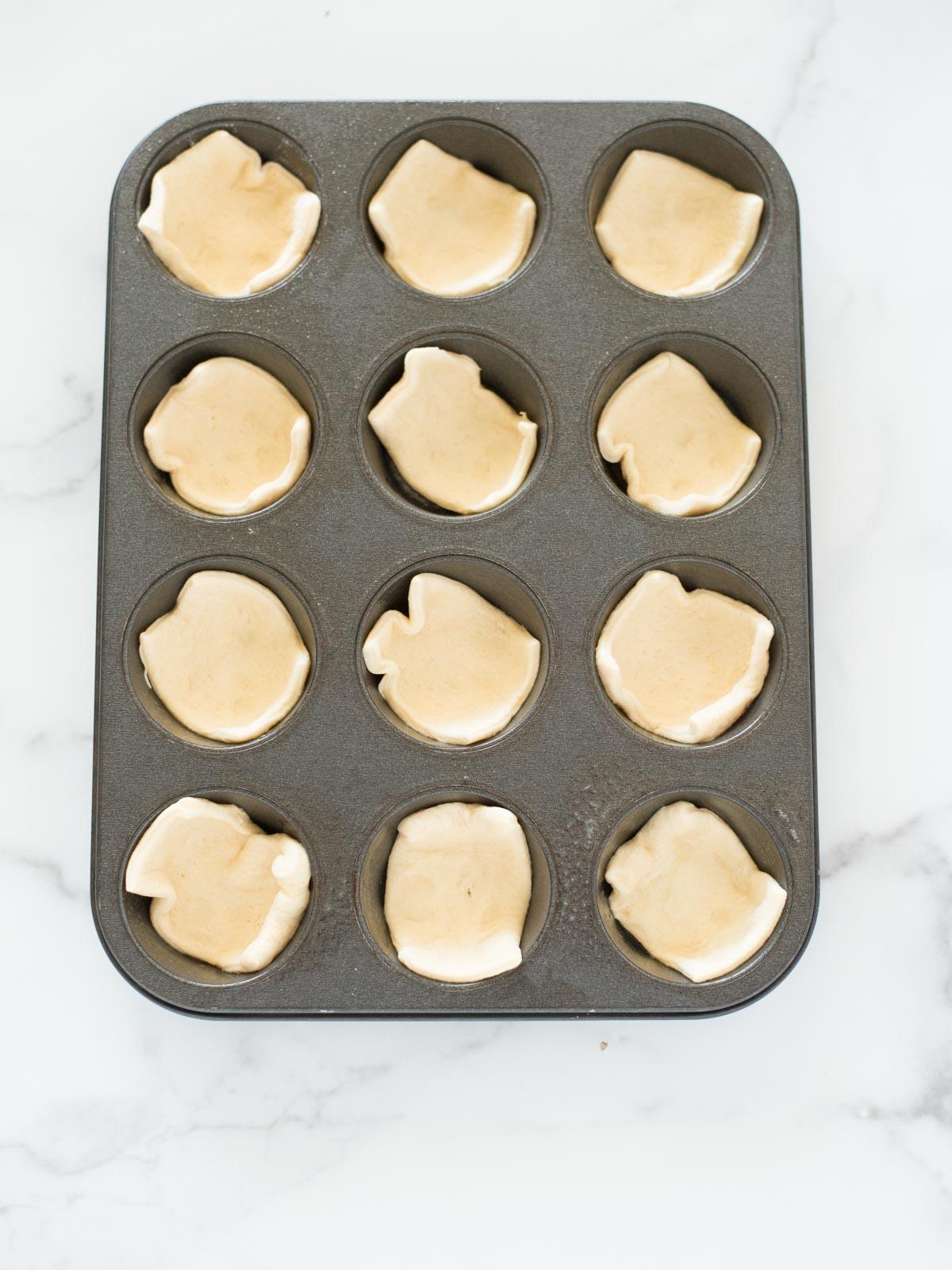 crescent roll dough in a muffin tin