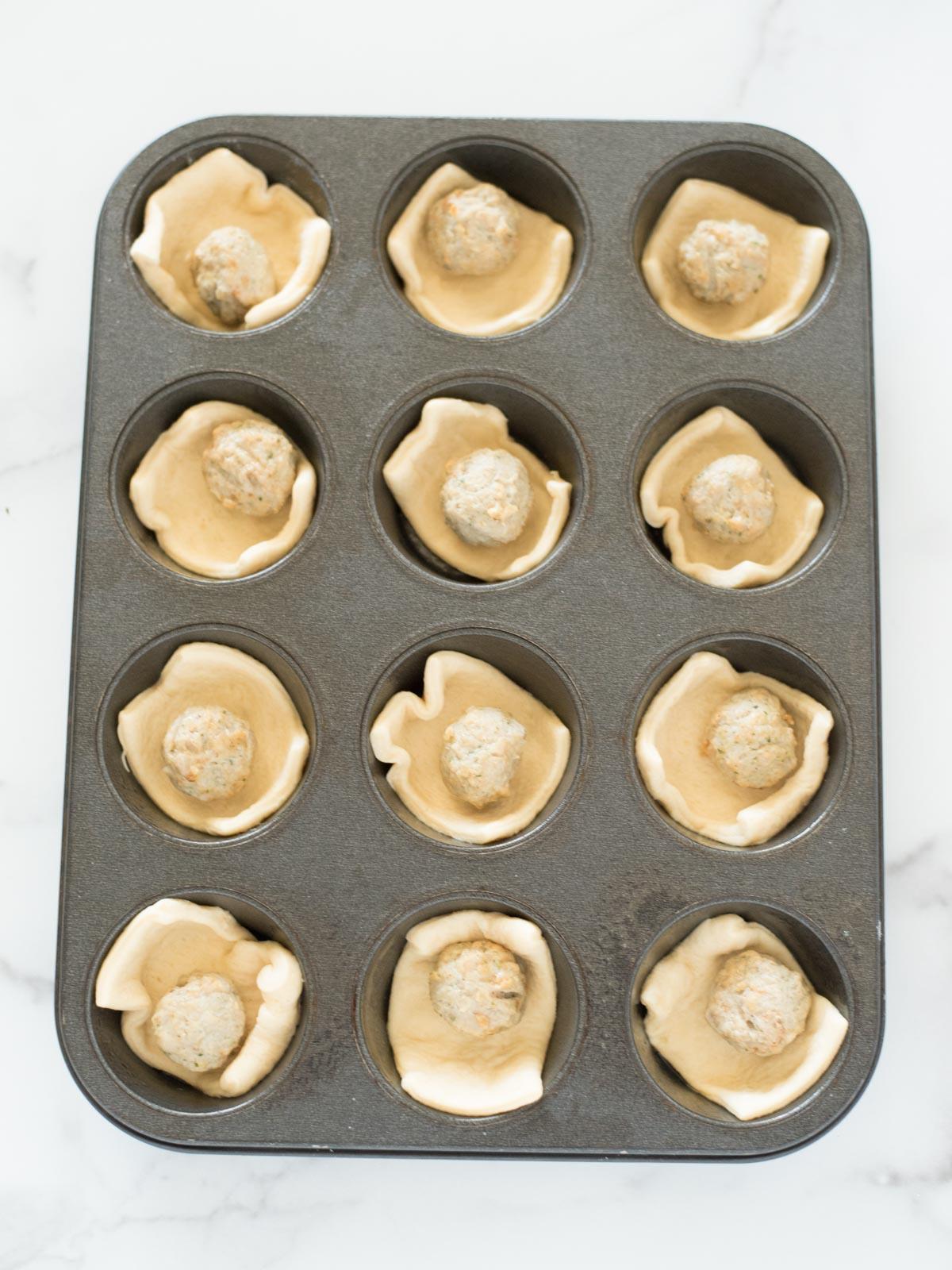 meatballs in crescent dough in a muffin tin