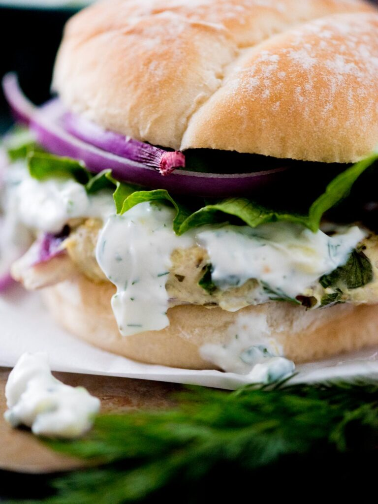 greek turkey burger in a bun topped with tzatziki sauce, red onion, and lettuce