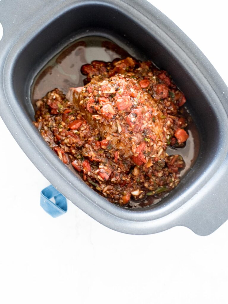 beef in crockpot with sauce poured over