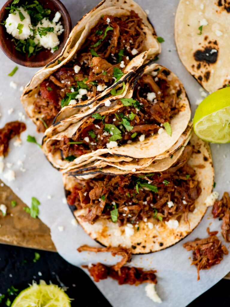 mexican shredded beef inside tacos topped with cilantro and queso fresco