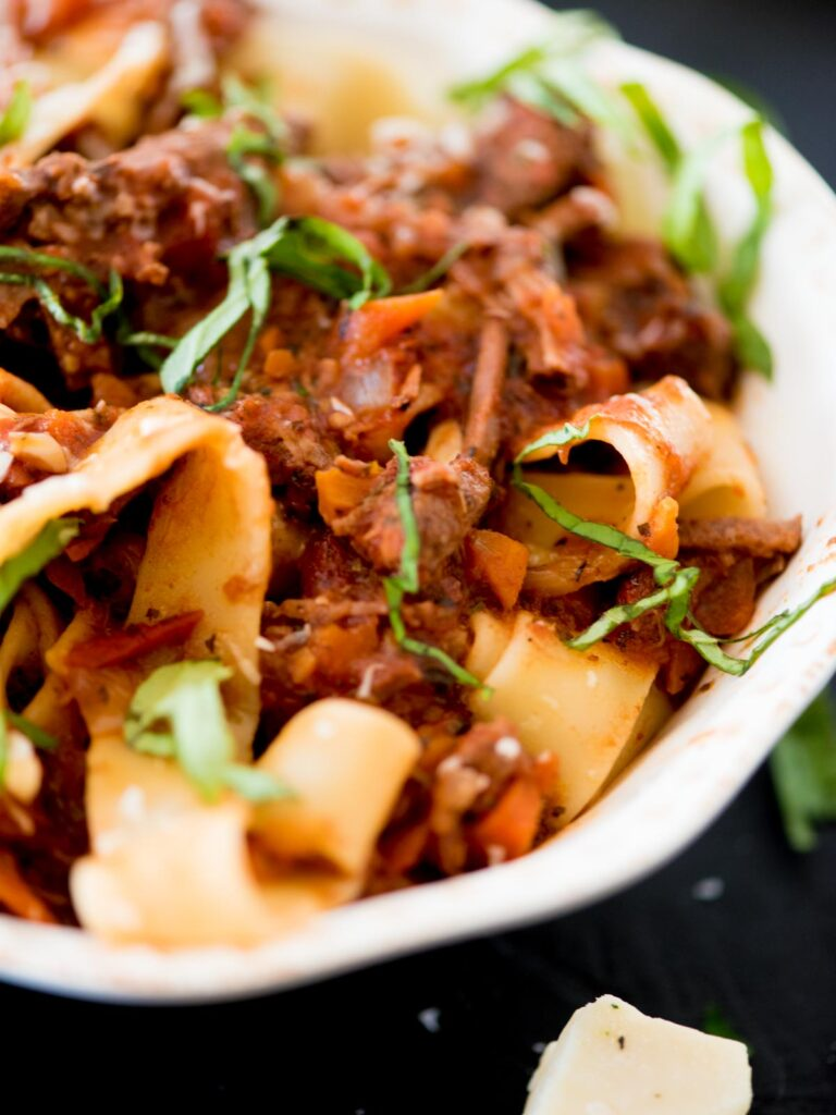 beef ragu over pasta topped with basil and parmesan
