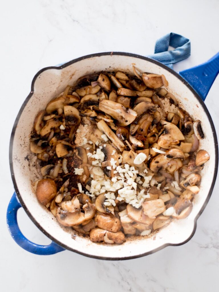 garlic added to sauteed mushrooms in a skillet