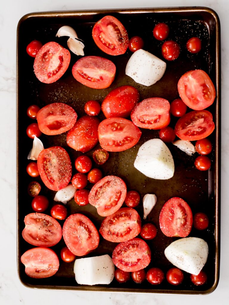 roma tomatoes, cherry tomatoes, garlic, and onion on a sheet pan sprinkled with olive oil, salt, and pepper