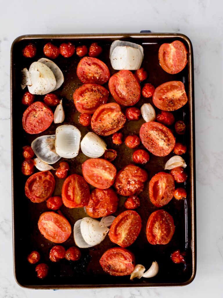 tomatoes, onion, and garlic that have been roasted on a sheet pan with olive oil, salt, and pepper