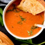 roasted tomato basil soup in a bowl topped with basil and a grilled cheese dipped in