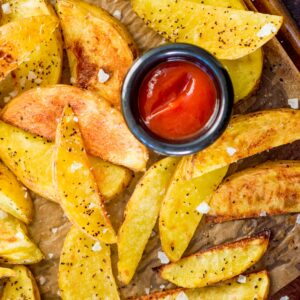 crispy oven baked garlic potato wedges with flaky sea salt on a baking sheet with ketchup
