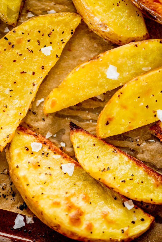 crispy oven baked garlic potato wedges with flaky sea salt on a baking sheet