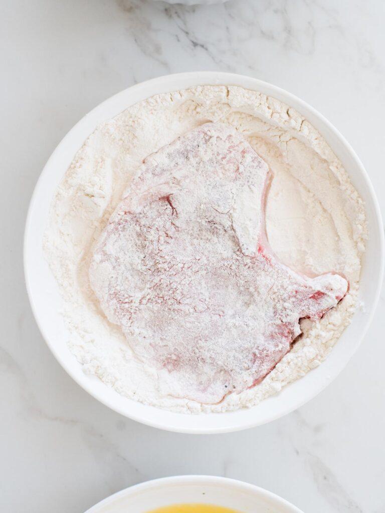 pork chop being dredged in flour