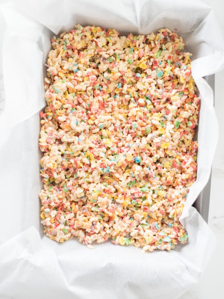 fruity pebbles rice krispie treats smoothed into a 9x13 pan