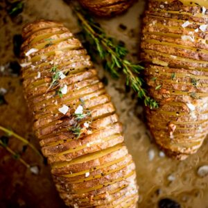 garlic butter hasselback potatoes topped with fresh thyme and flaked salt