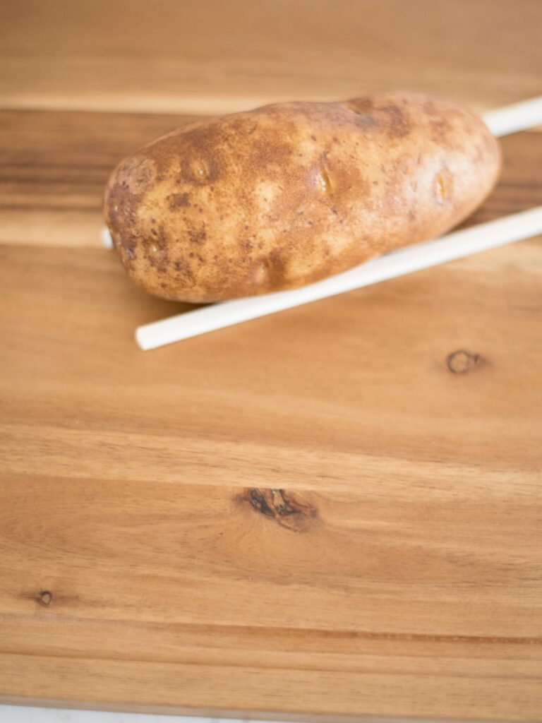 russet potato on chopsticks