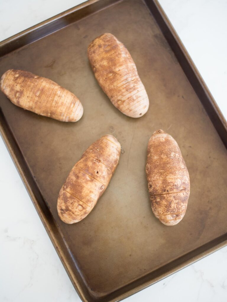 sliced hasselback potatoes on a baking sheet
