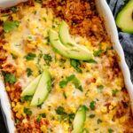 mexican rice casserole topped with cilantro and avocado