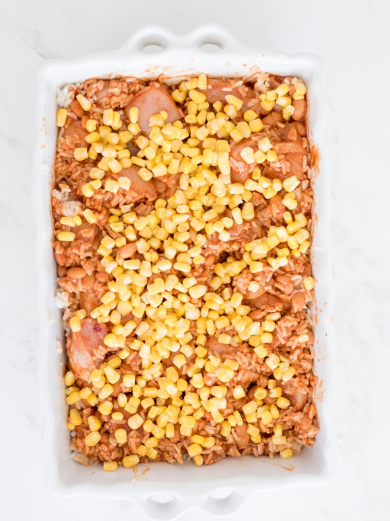 corn sprinkled over the top of the chicken rice and beans mix