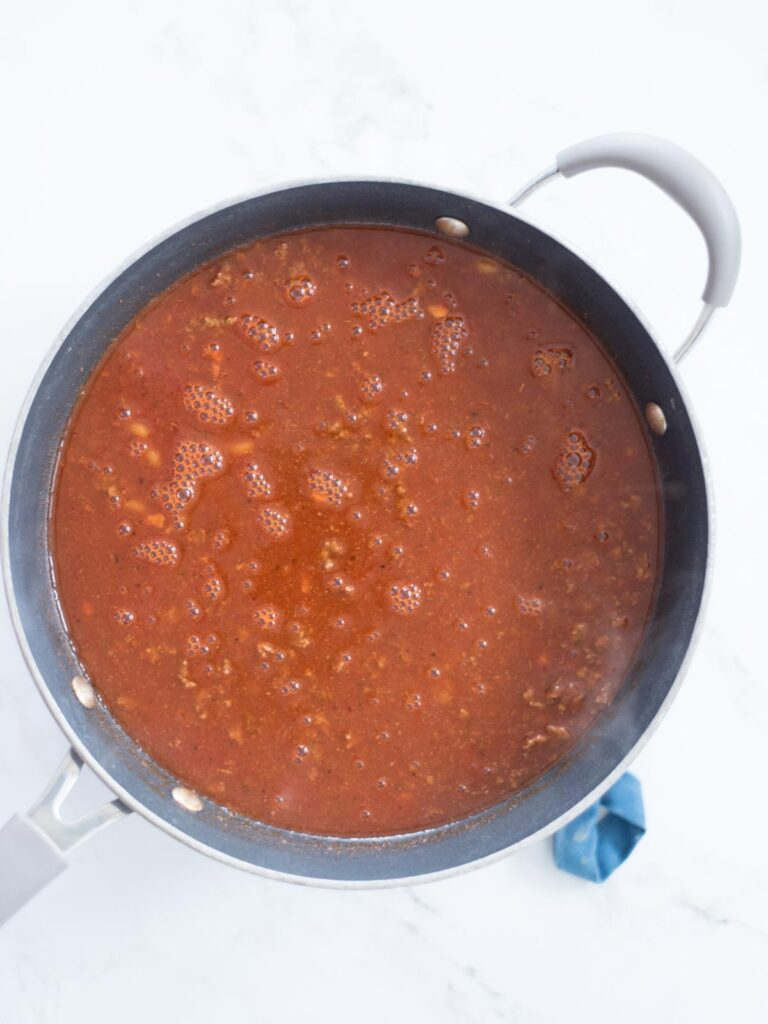 enchilada sauce, beef broth, and tomato sauce added to skillet with ground beef