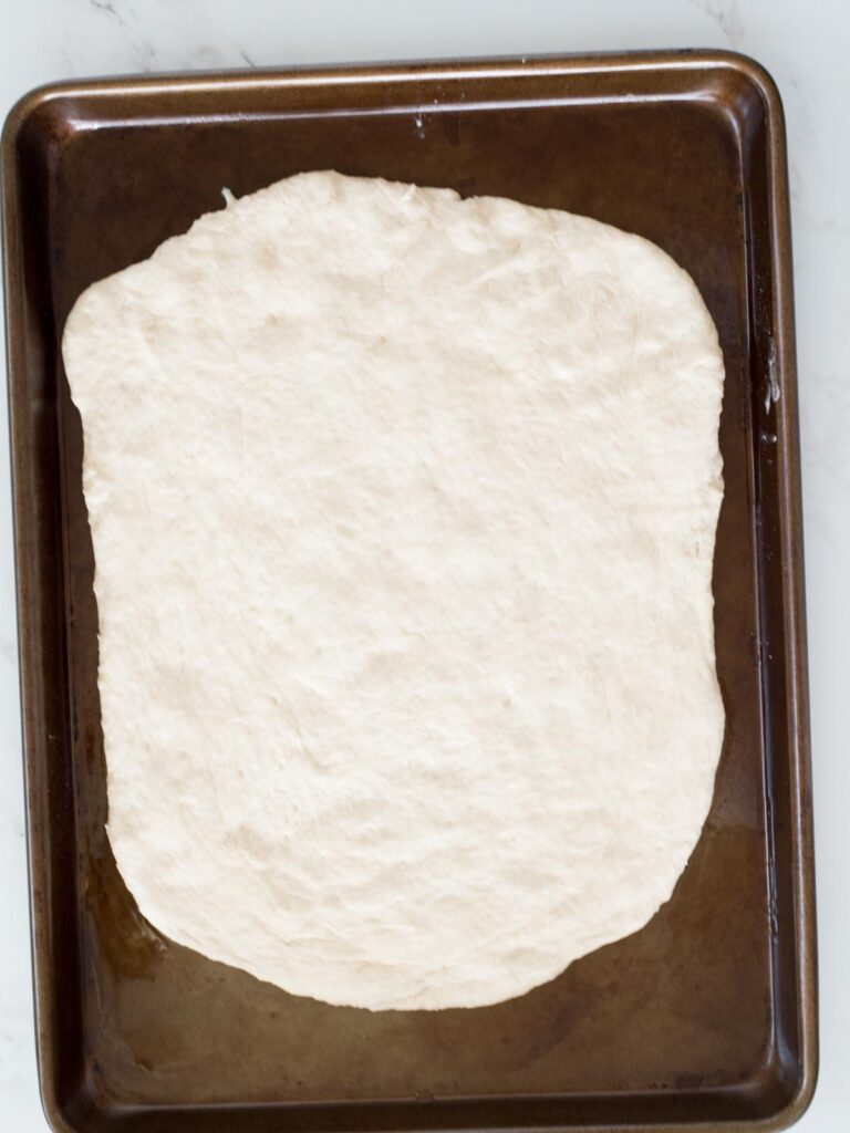 dough spread out on a baking sheet