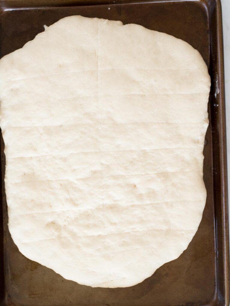 scored dough risen on a baking sheet