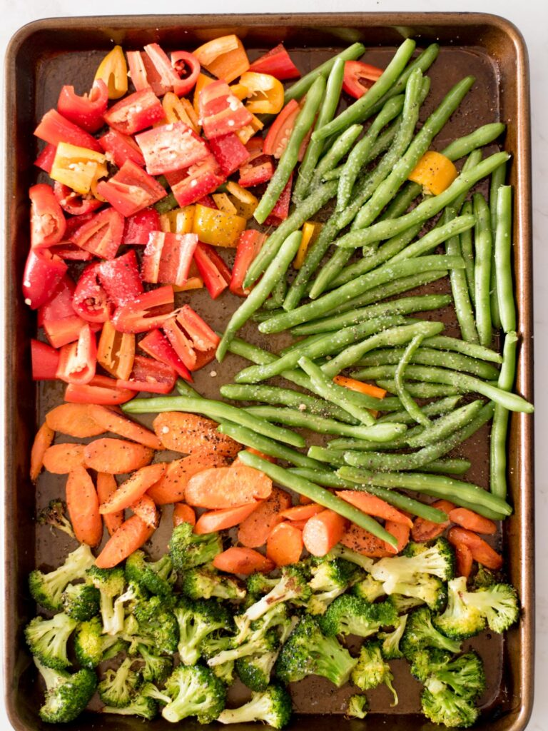 bell pepper, green beans, carrots, and broccoli on a sheet pan seasoned with salt and pepper