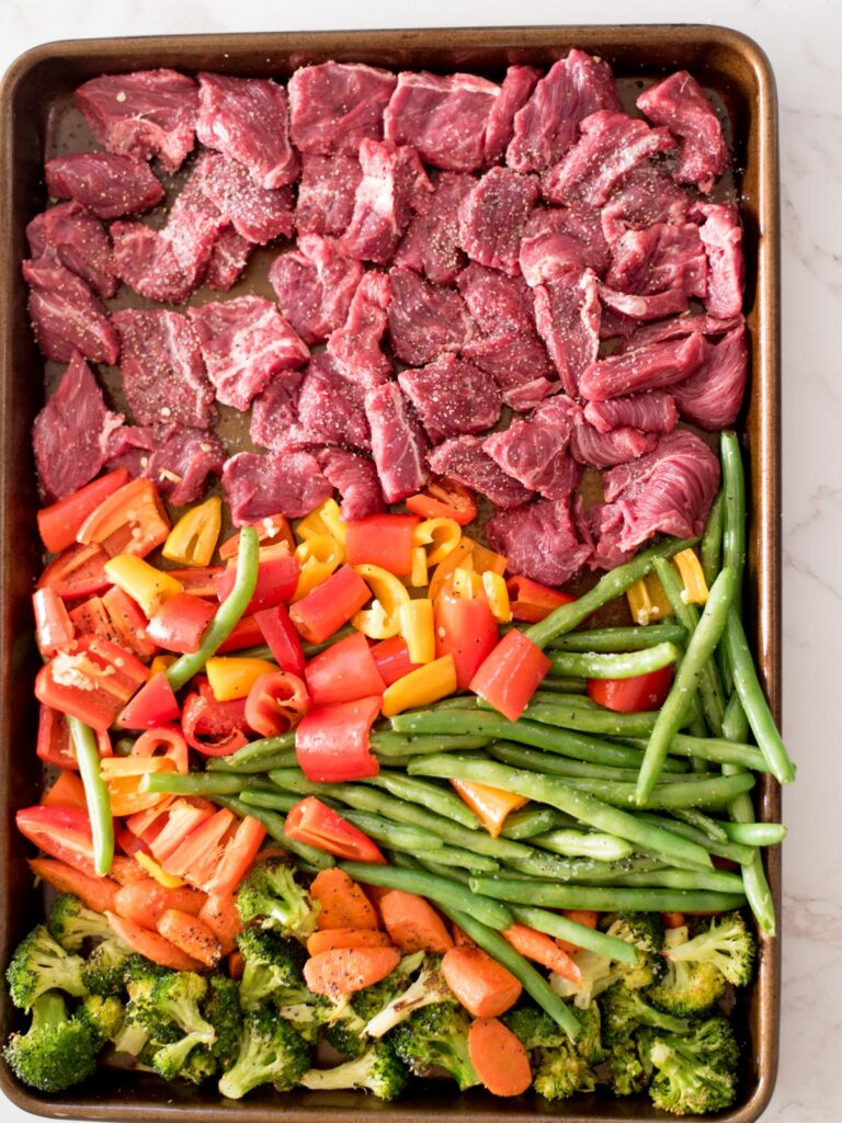 broccoli, carrots, green beans, bell pepper, and beef on a sheet pan