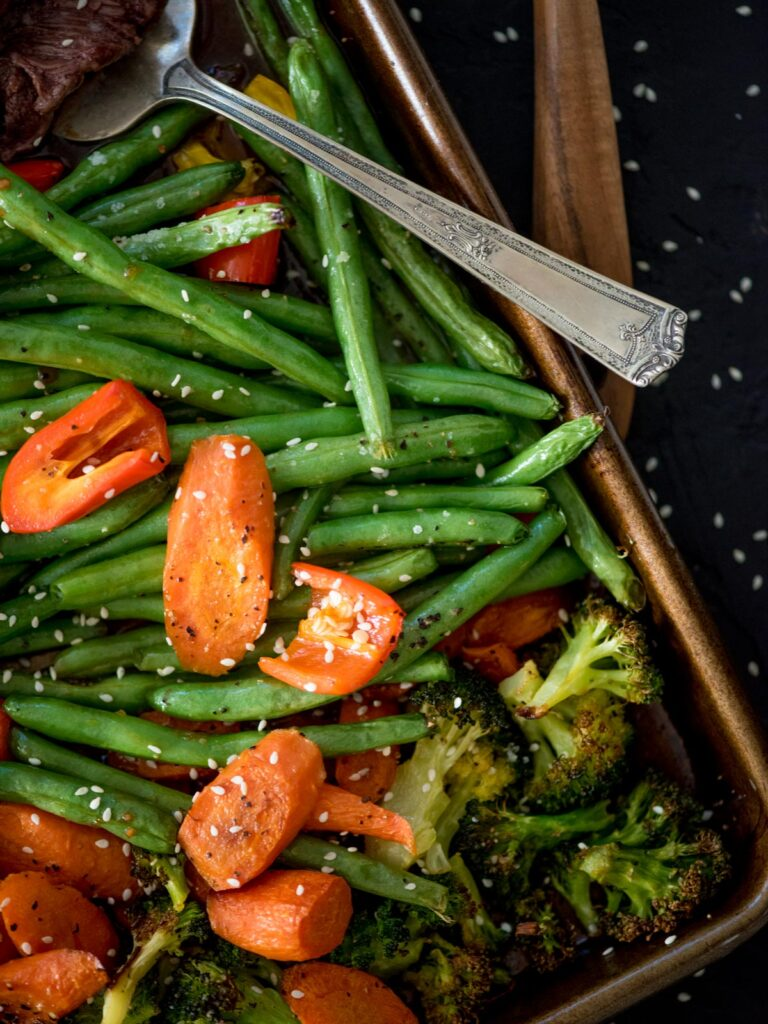 carrots, green beans and broccoli cooked on a sheet pan