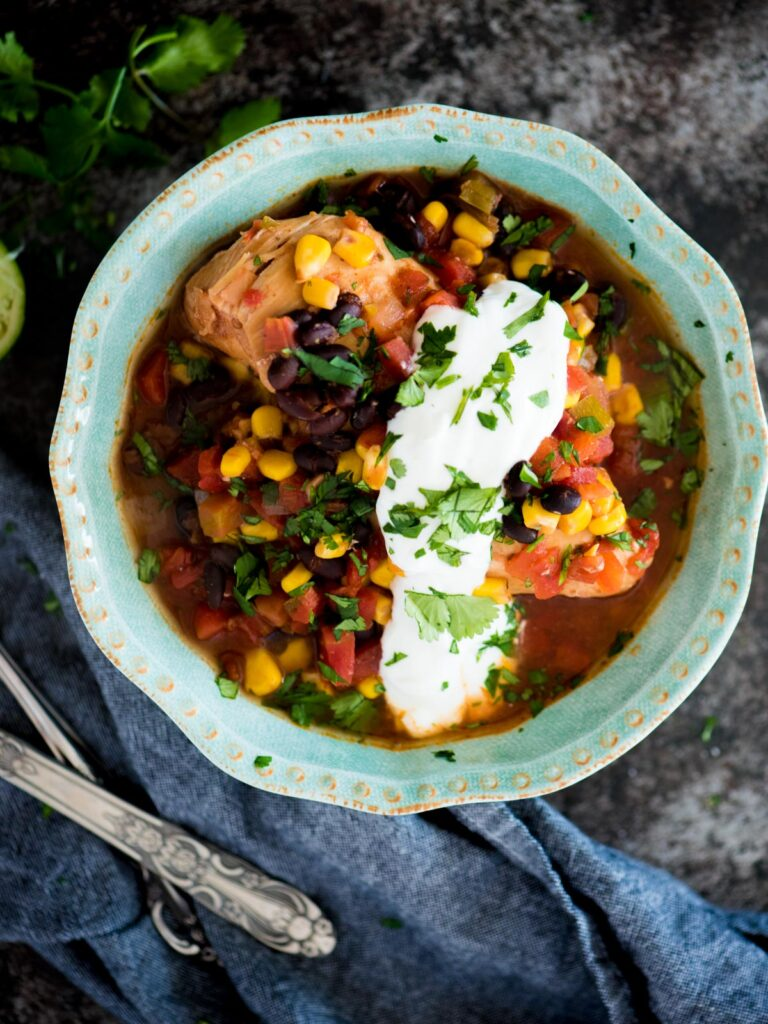 slow cooker mexican chicken in a bowl topped with cilantro and sour cream